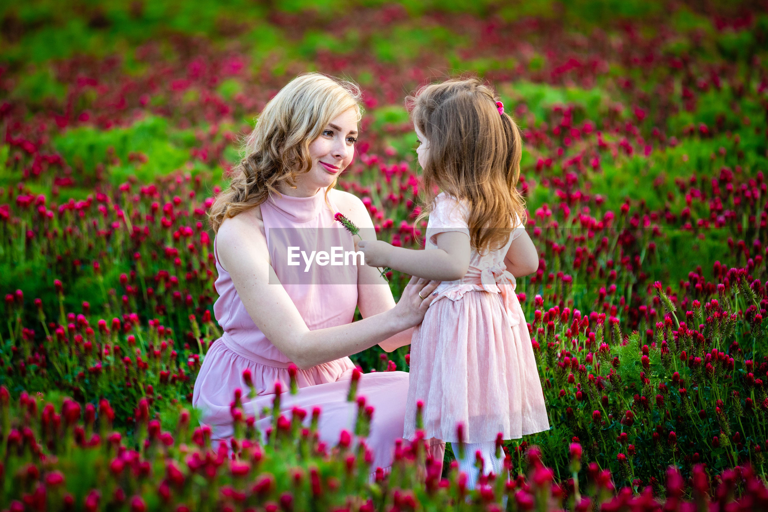 Mother and daughter amidst pink flowers
