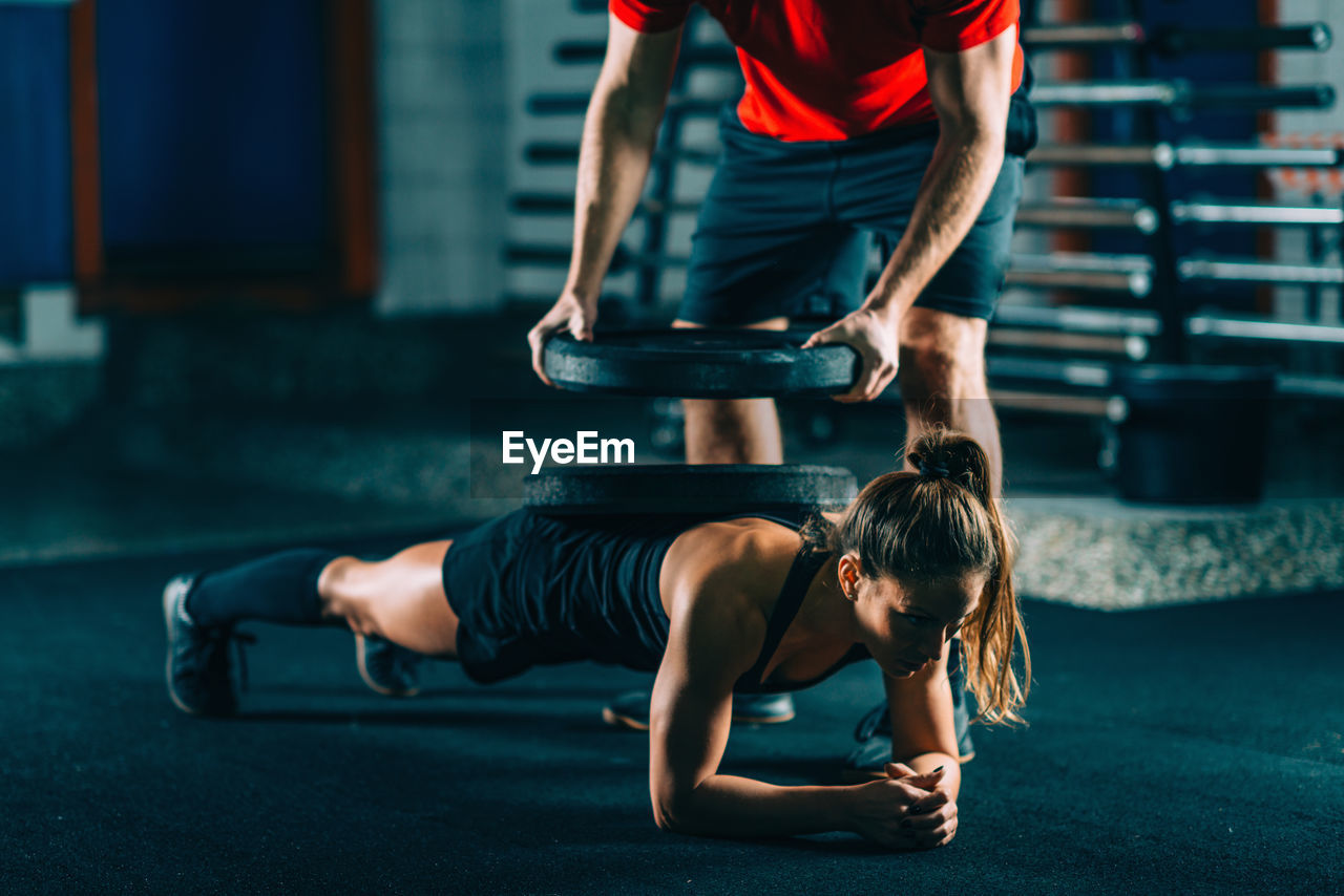 Instructor Putting Weights On Woman Exercising At Gym
