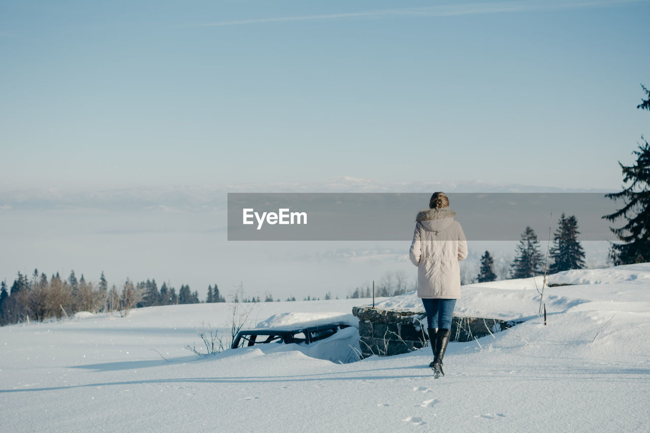 cold temperature, winter, snow, one person, sky, full length, real people, standing, beauty in nature, leisure activity, lifestyles, scenics - nature, nature, day, field, non-urban scene, warm clothing, land, tree, outdoors