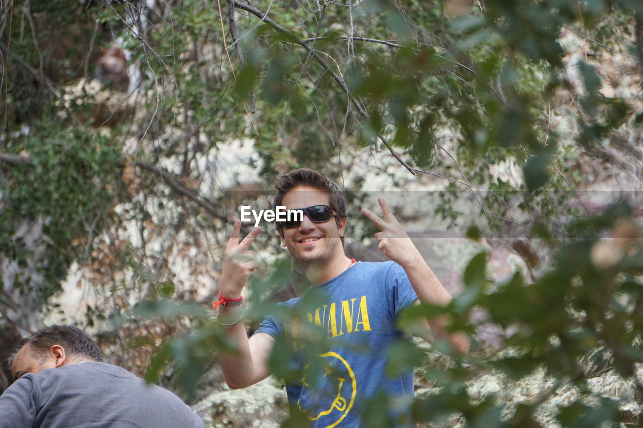 Portrait Of Man In Sunglasses Gesturing Peace Signs Amidst Trees In Forest