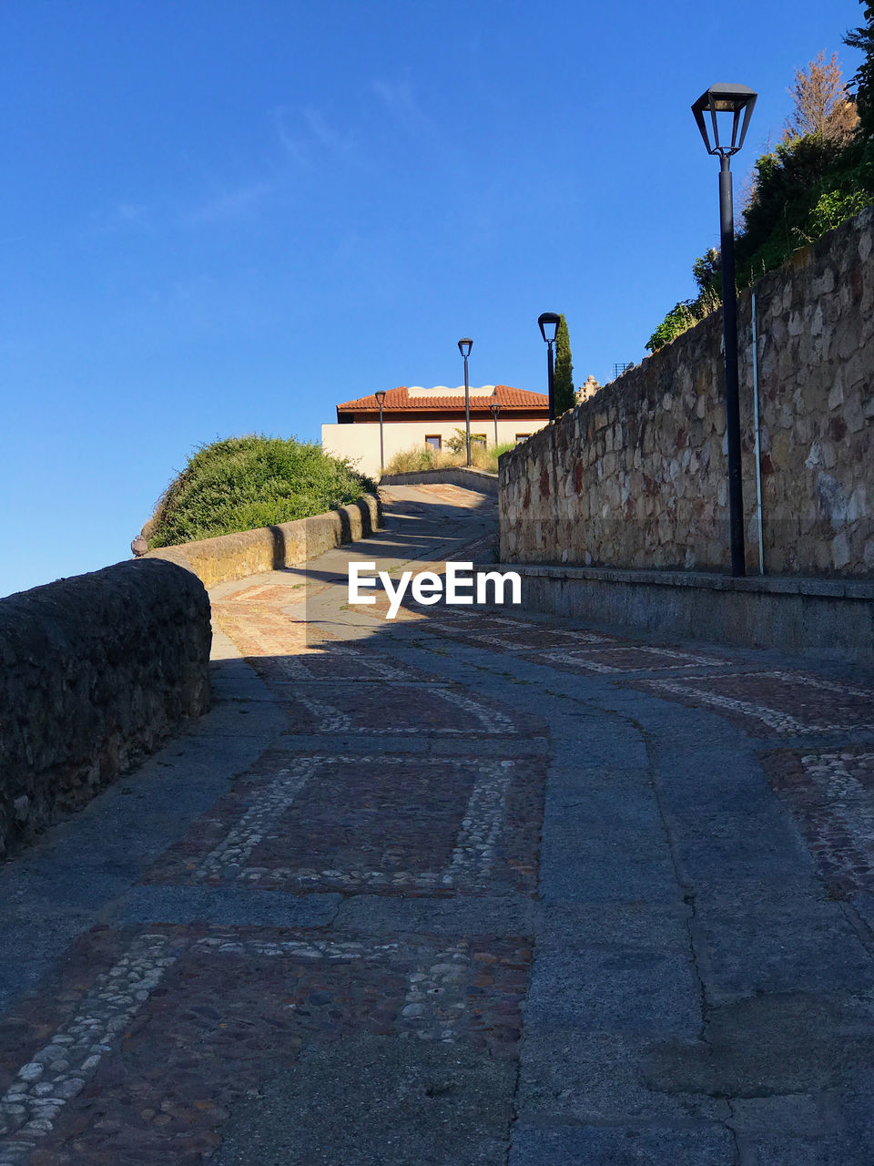 sky, architecture, built structure, street light, clear sky, nature, sunlight, blue, the way forward, no people, direction, day, history, the past, street, wall, building exterior, footpath, shadow, lighting equipment, outdoors, stone wall