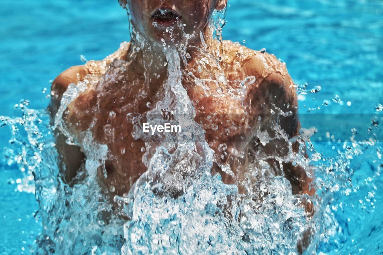 Water Splashing On Boy In Swimming Pool