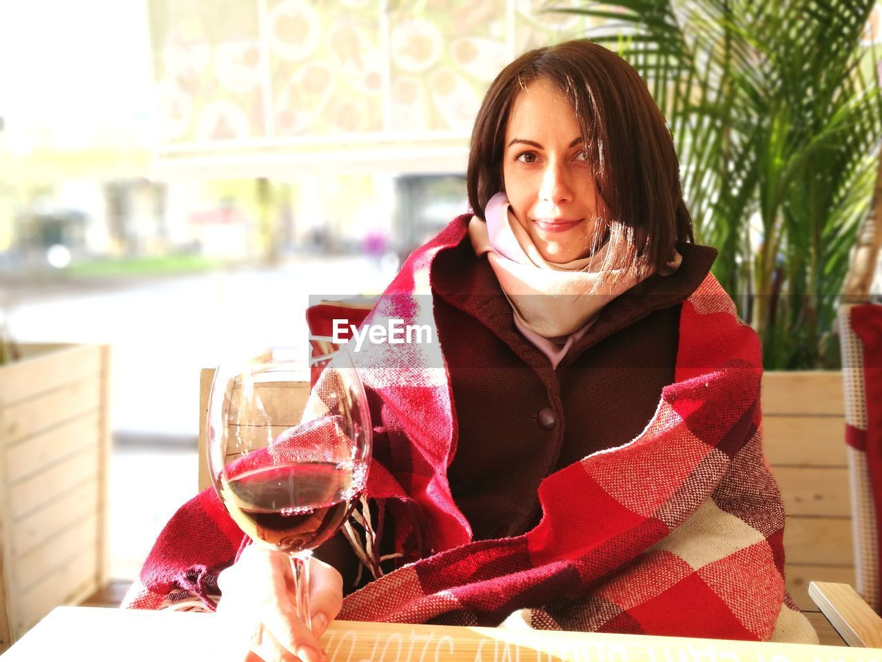 Portrait of young woman in warm clothing having wine while sitting at home