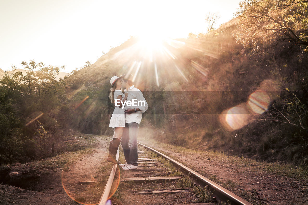 lens flare, sunlight, sunbeam, two people, railroad track, sun, togetherness, full length, real people, outdoors, leisure activity, rail transportation, young adult, young women, day, clear sky, sunset, happiness, women, nature, tree, bonding, sky, adult, people, adults only