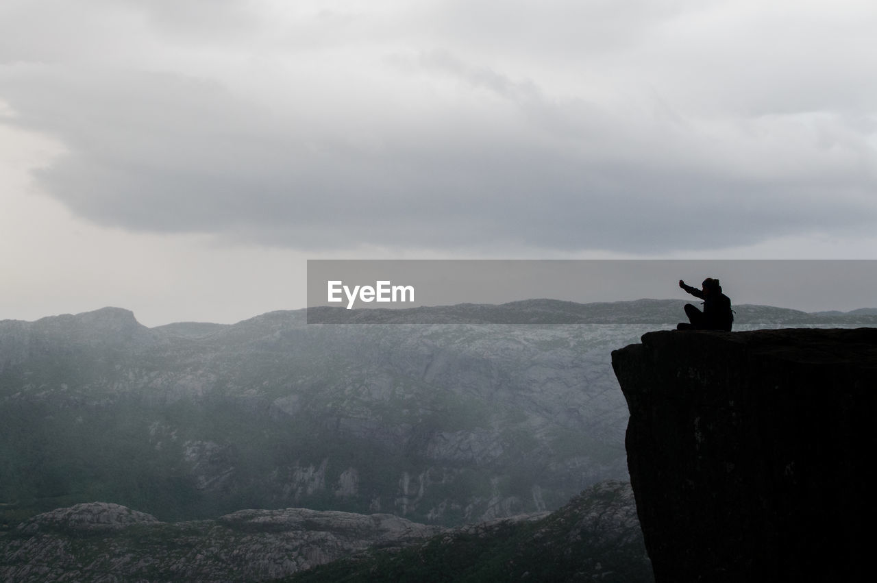 Silhouette man sitting on mountain against sky