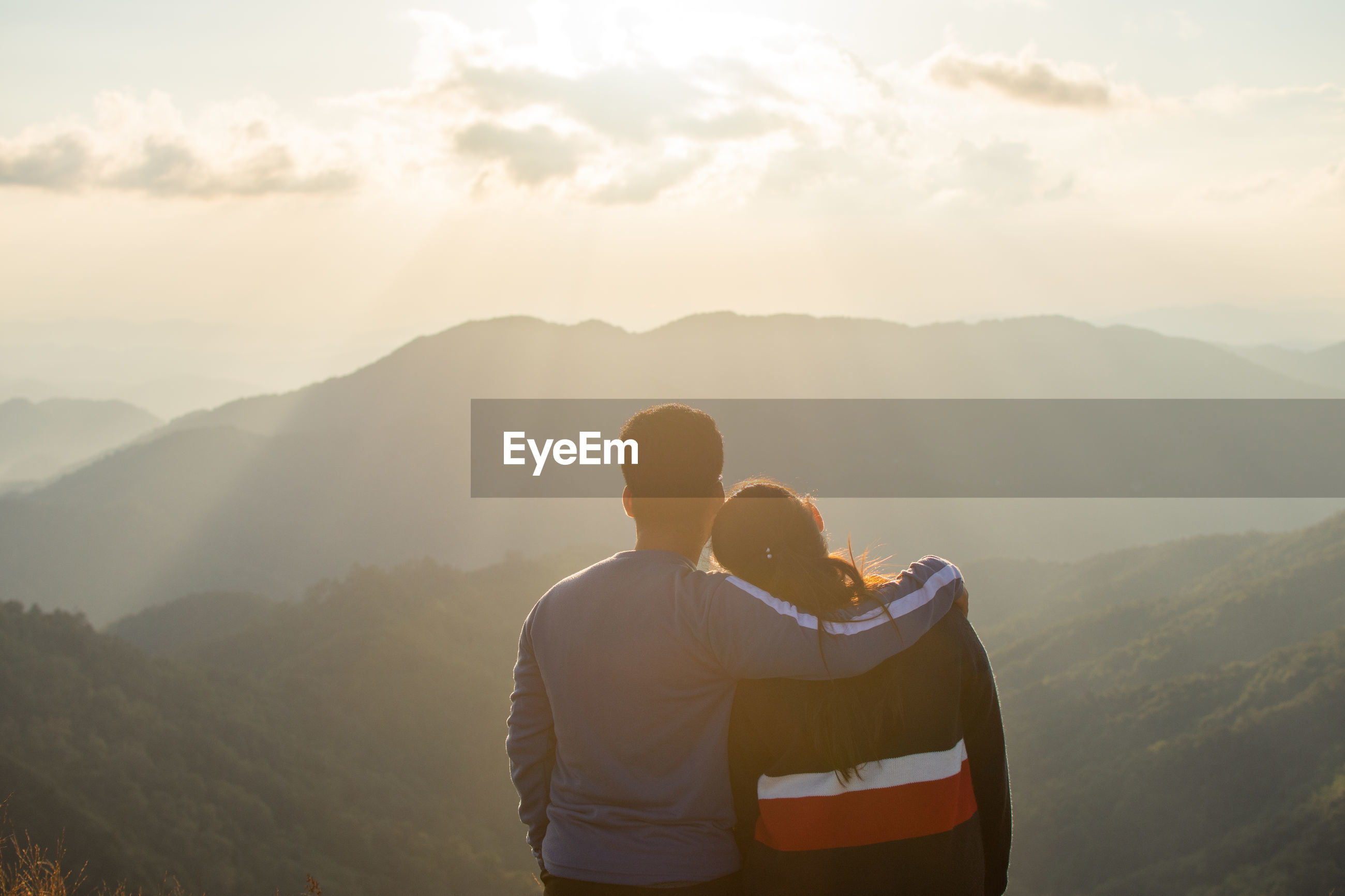 Rear view of couple looking at mountains against cloudy sky