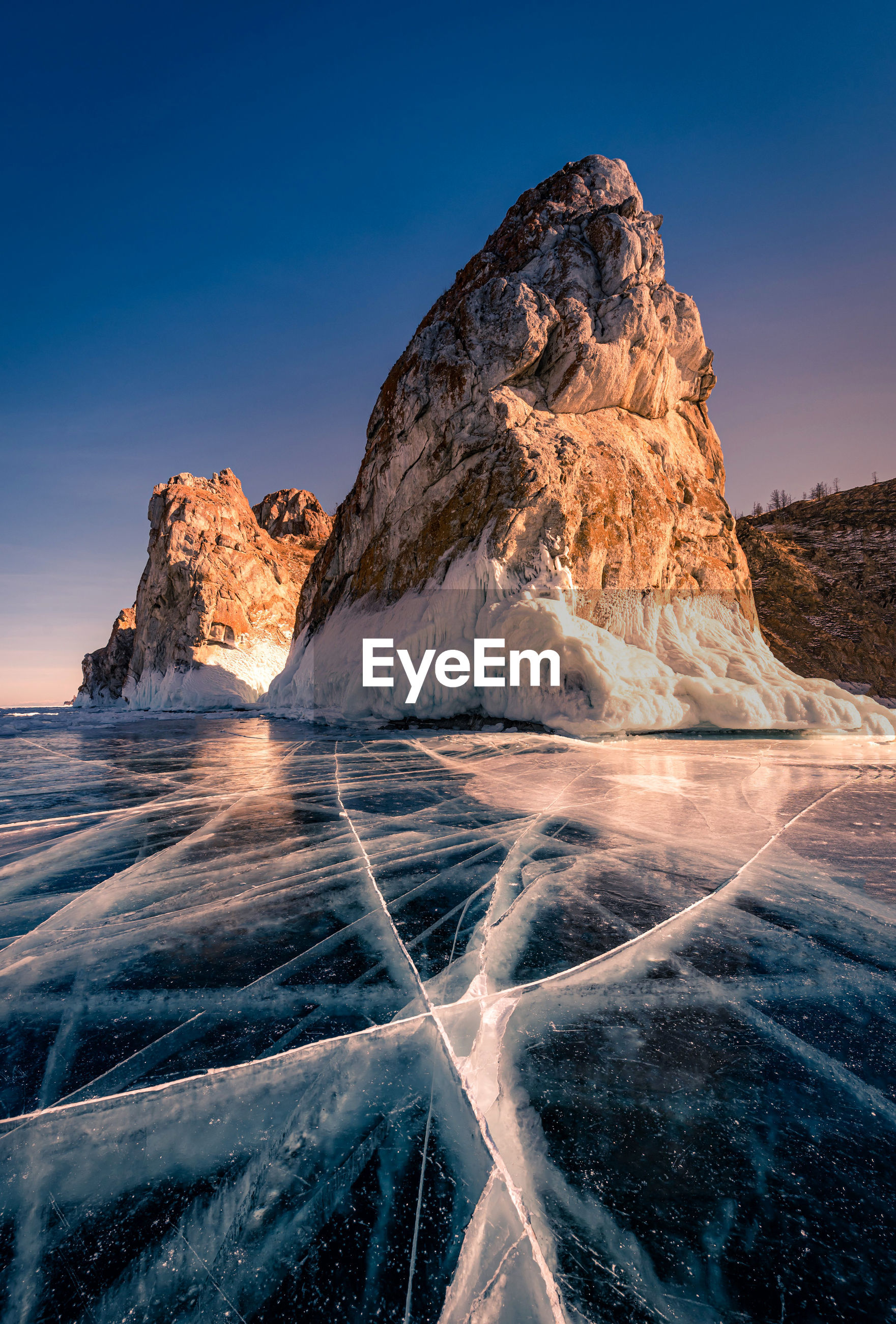 Scenic view of frozen sea by rock formation against blue sky