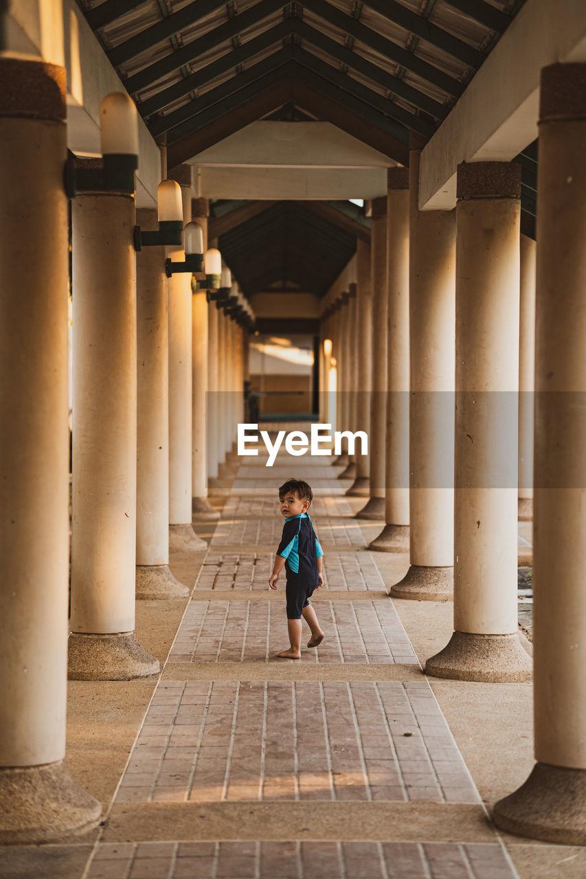 Full length of boy walking in corridor of building