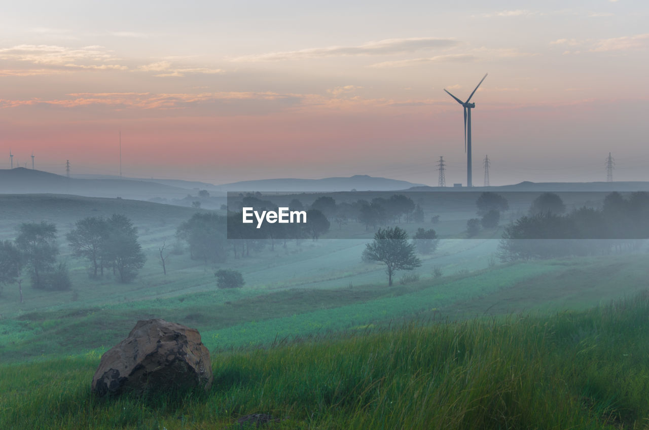 Scenic View Of Wind Turbine Field Against Sky During Sunset