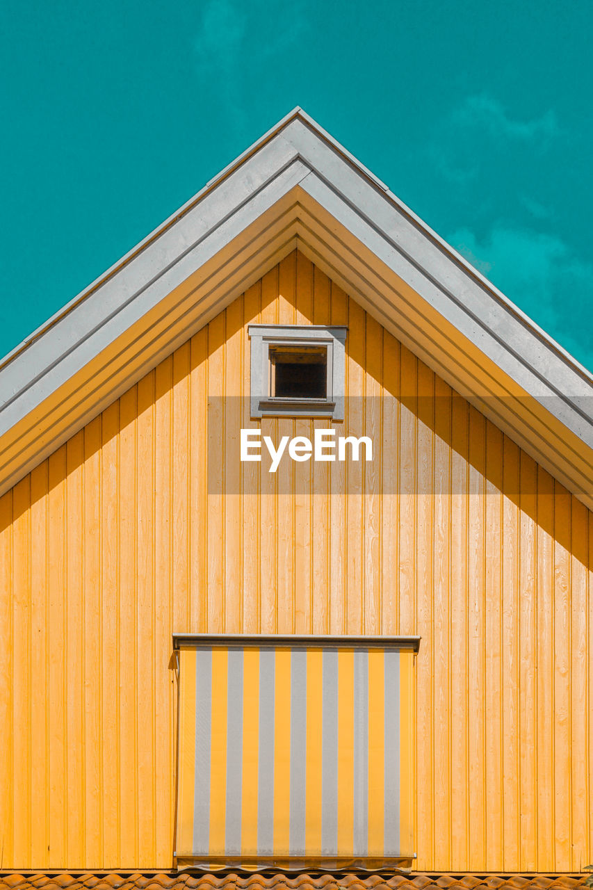 built structure, architecture, building exterior, no people, day, building, yellow, sunlight, nature, wood - material, brown, outdoors, low angle view, orange color, window, pattern, house, sky, blue, roof, corrugated