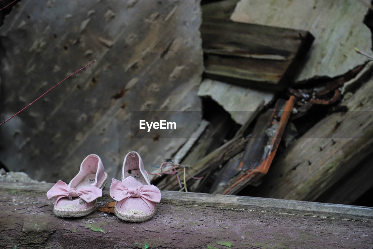 wood - material, day, shoe, no people, focus on foreground, close-up, built structure, pink color, outdoors, old, architecture, nature, pair, still life, abandoned, rusty, weathered, metal, wall - building feature, obsolete