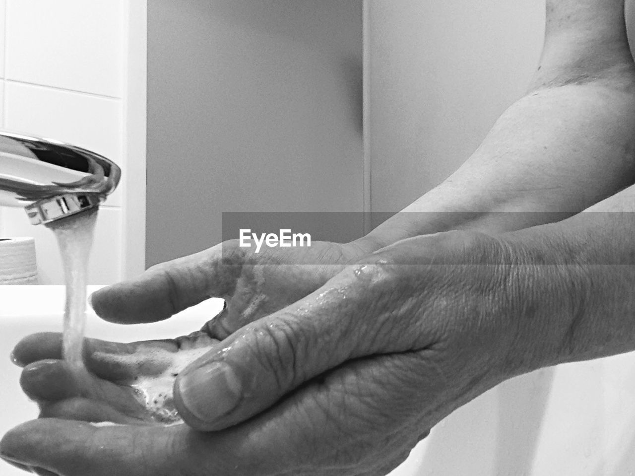 Cropped Image Of Man Washing Hands In Bathroom At Home