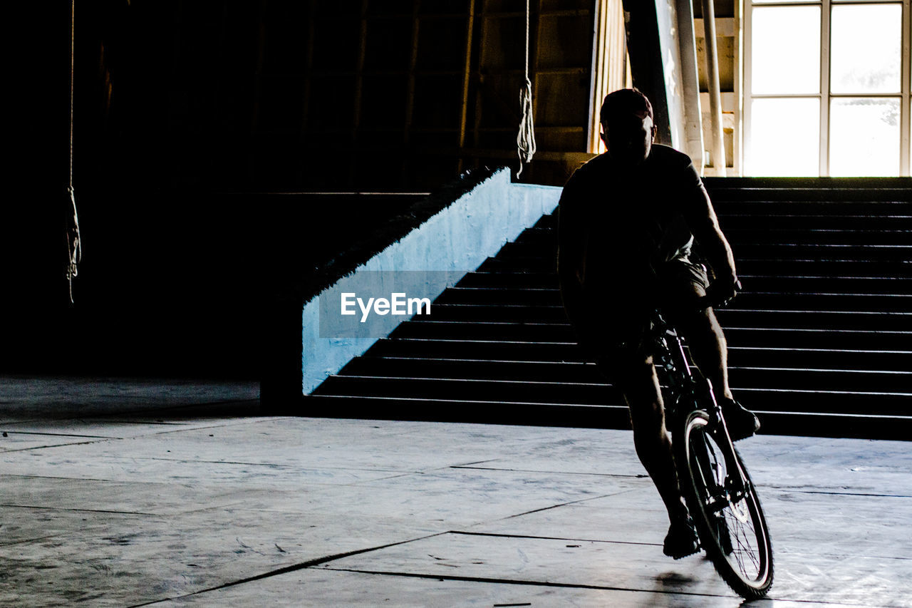 High Angle View Of Man Cycling On Tiled Floor