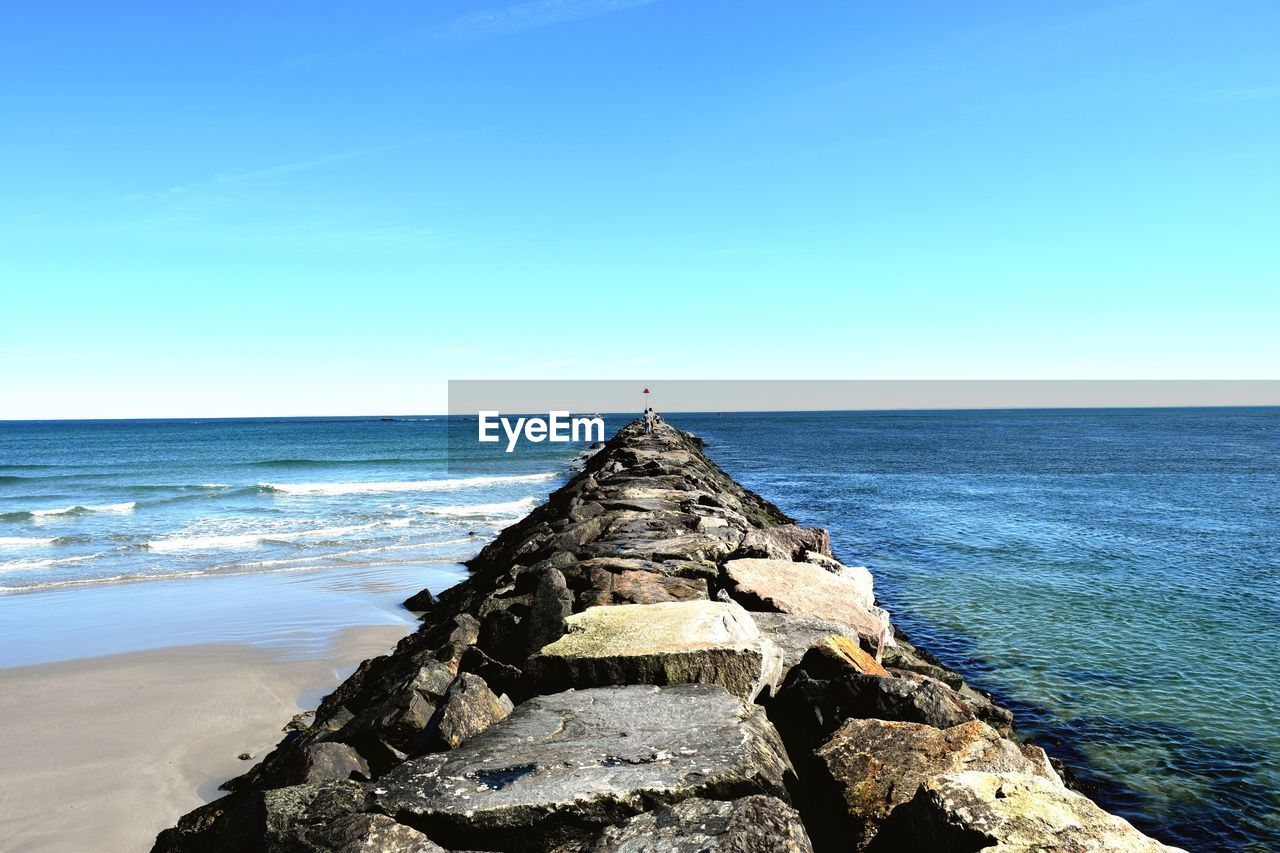 sea, water, sky, horizon over water, horizon, scenics - nature, beauty in nature, tranquil scene, tranquility, nature, rock, clear sky, blue, day, rock - object, solid, idyllic, land, beach, no people, groyne, outdoors
