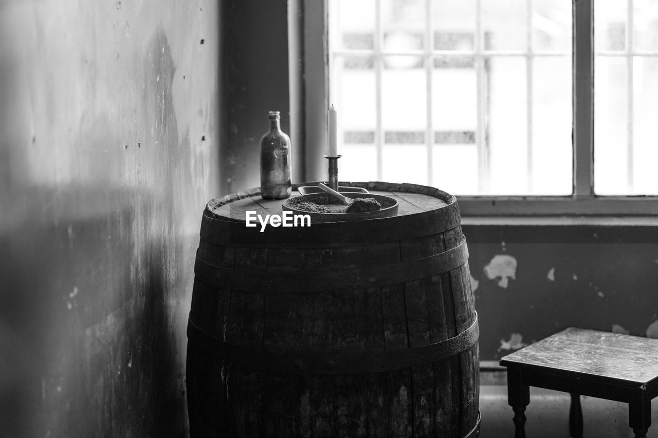 window, container, indoors, focus on foreground, day, metal, no people, cylinder, still life, barrel, table, close-up, wood - material, old, craft, nature, storage, drum - container, glass - material