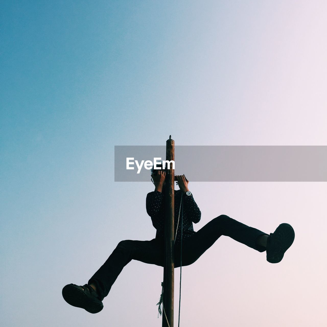 Low angle view of man climbing pole against clear sky