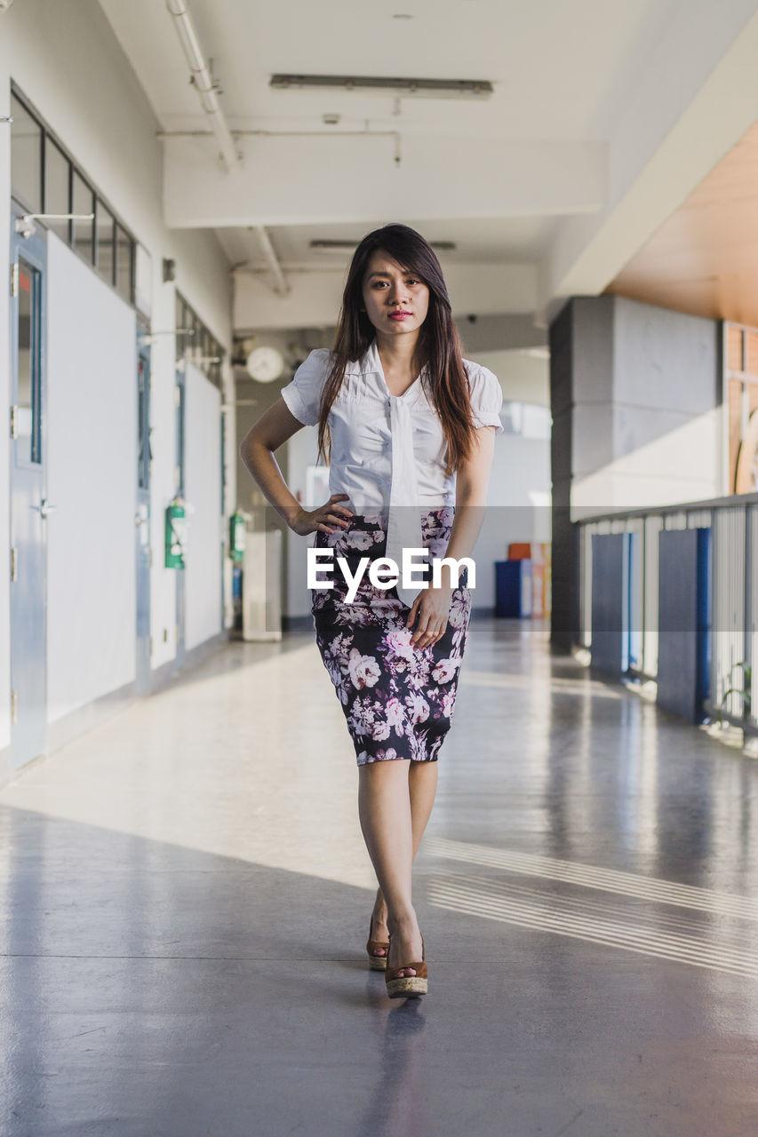 Portrait of young woman walking in corridor