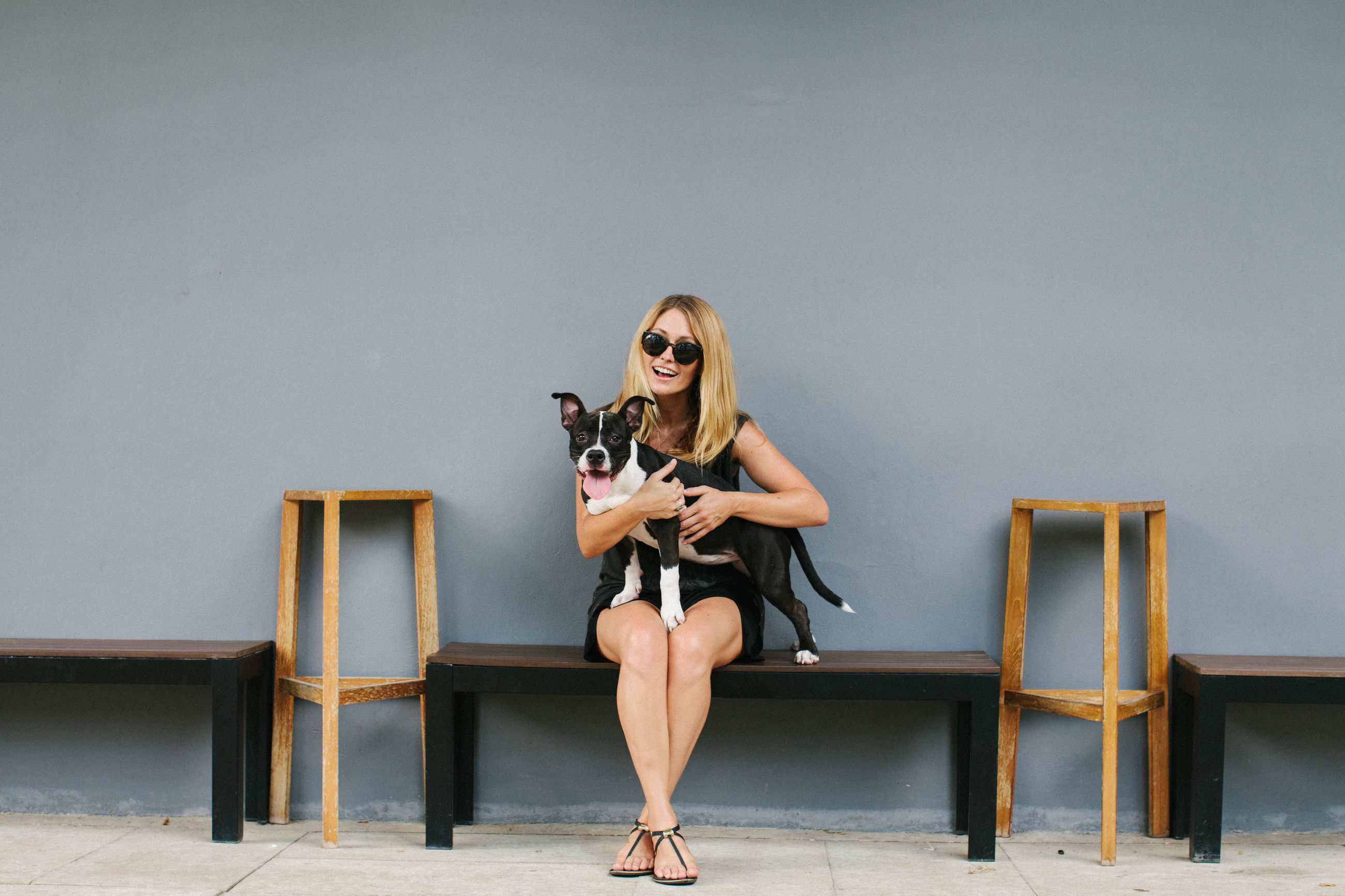 Young woman sitting on bench with her dog