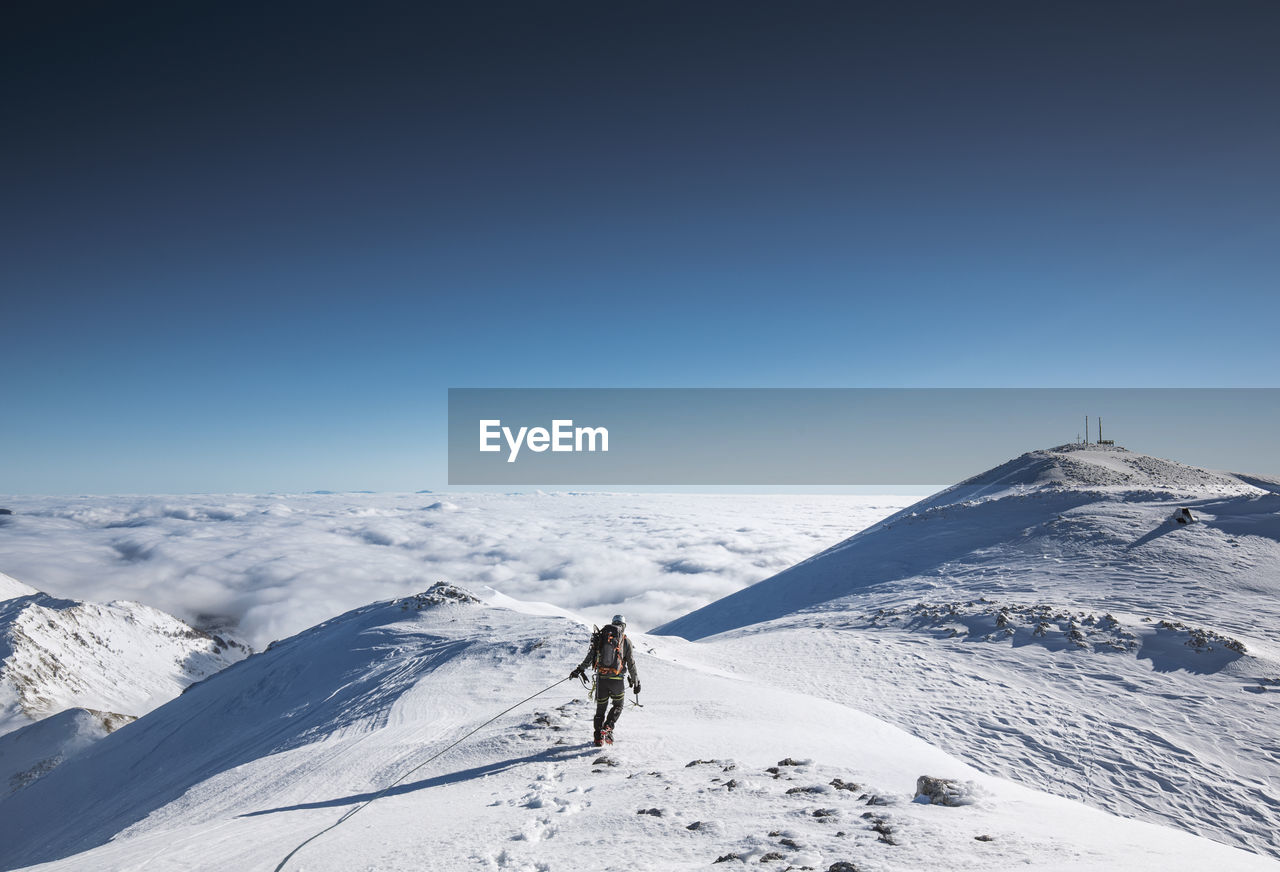 Man Walking On Snowcapped Mountain Against Blue Sky