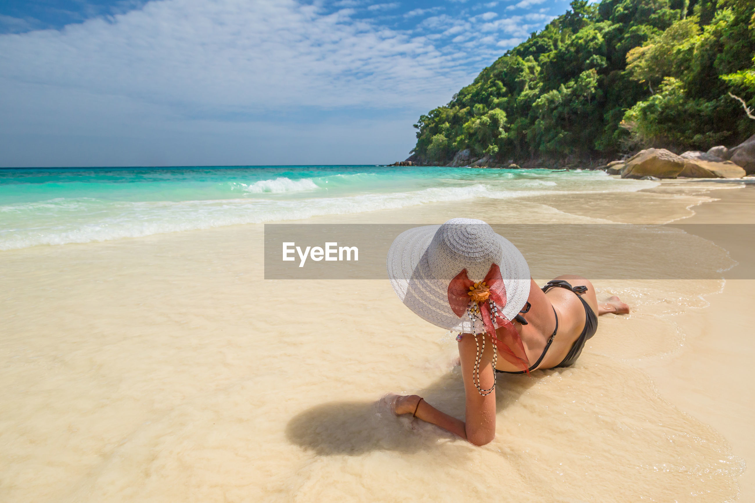 Woman relaxing at beach against sky