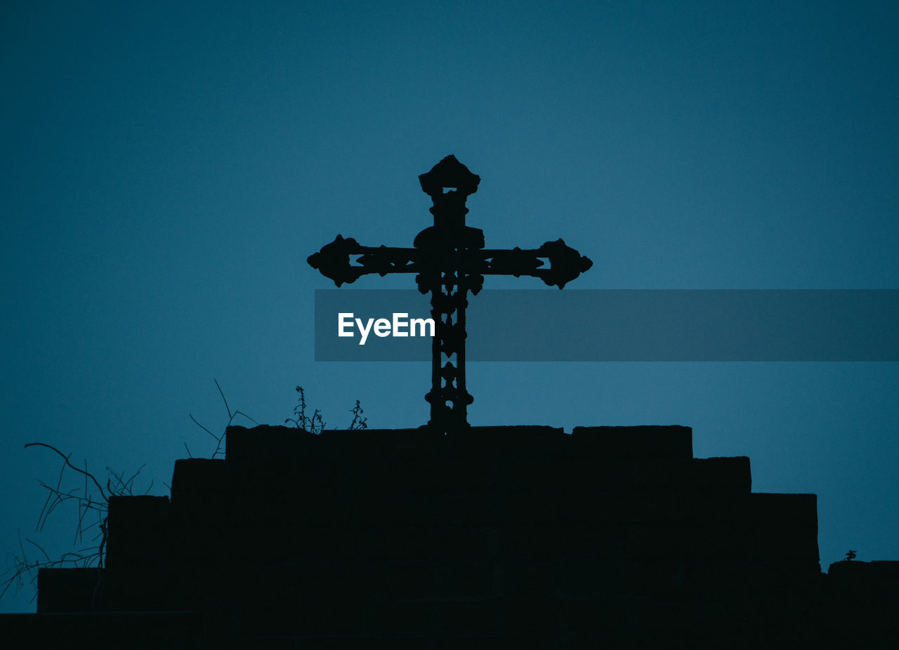 Low angle view of silhouette cross on field against clear blue sky