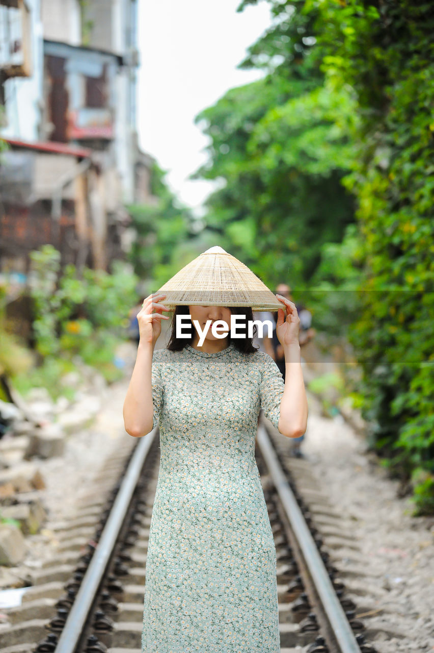 railroad track, track, rail transportation, one person, real people, transportation, lifestyles, focus on foreground, day, standing, women, casual clothing, nature, leisure activity, front view, plant, childhood, direction, tree, outdoors, diminishing perspective