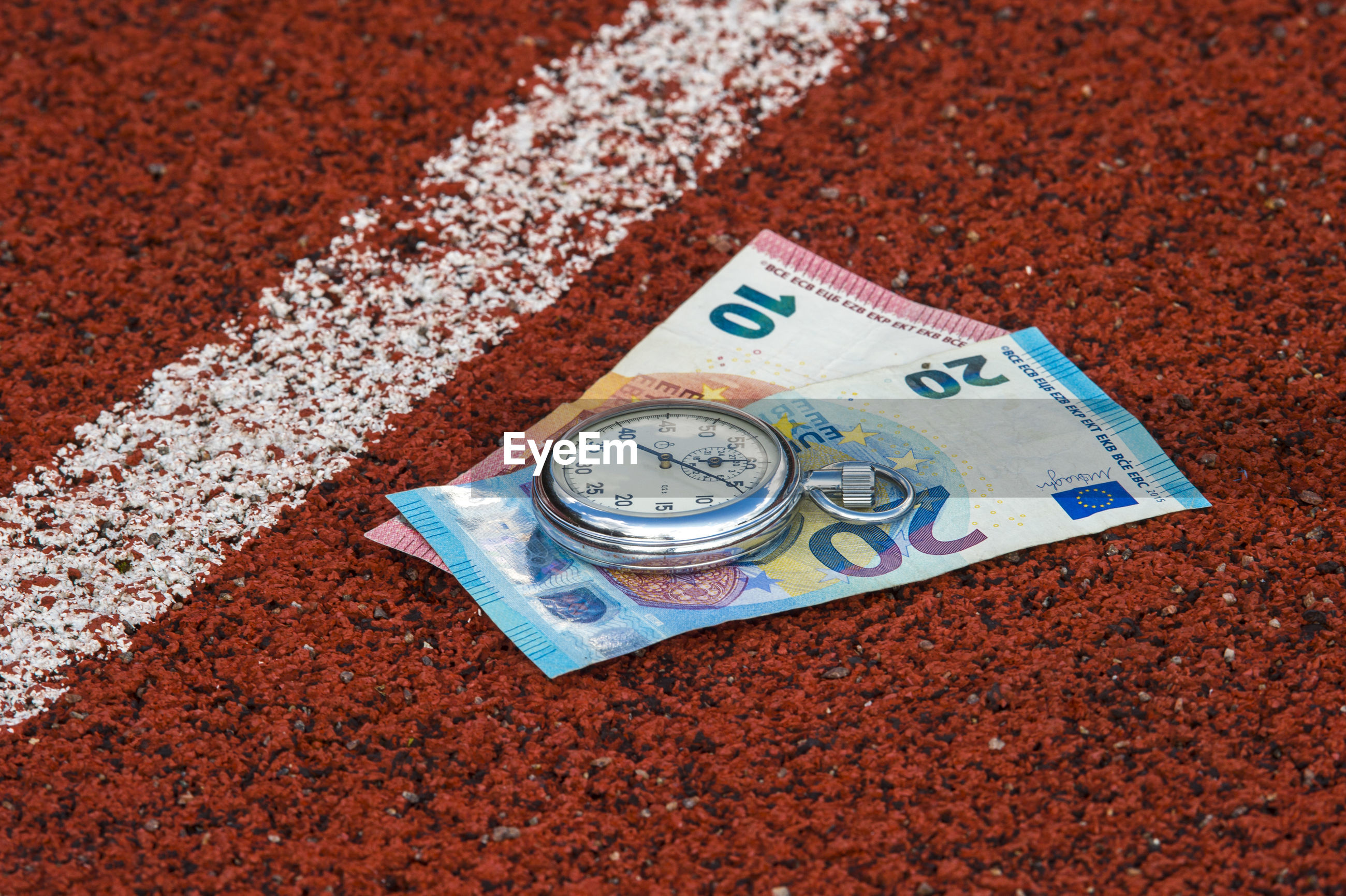 Close-up of stopwatch and paper currencies on field