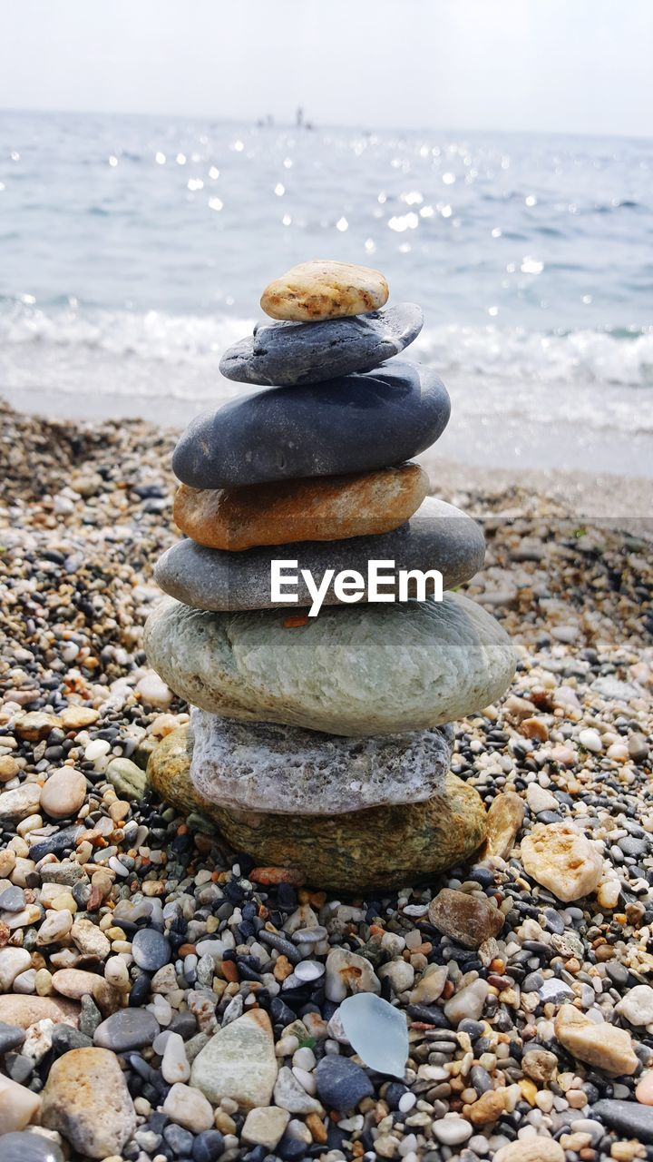 stone - object, pebble, solid, rock, beach, water, stone, stack, land, sea, balance, nature, rock - object, zen-like, no people, day, tranquility, sky, focus on foreground, outdoors, horizon over water, temptation