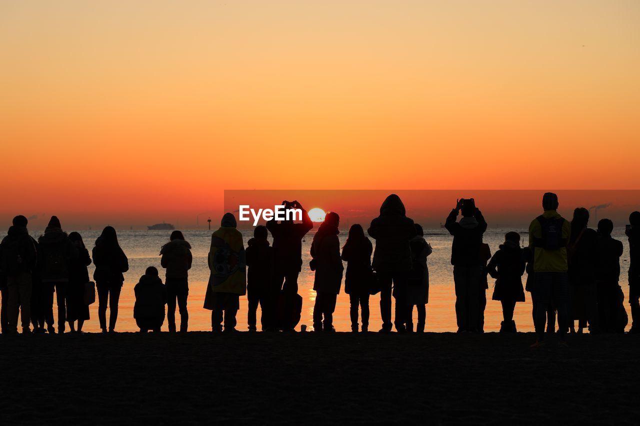 Silhouette people at beach against orange sky