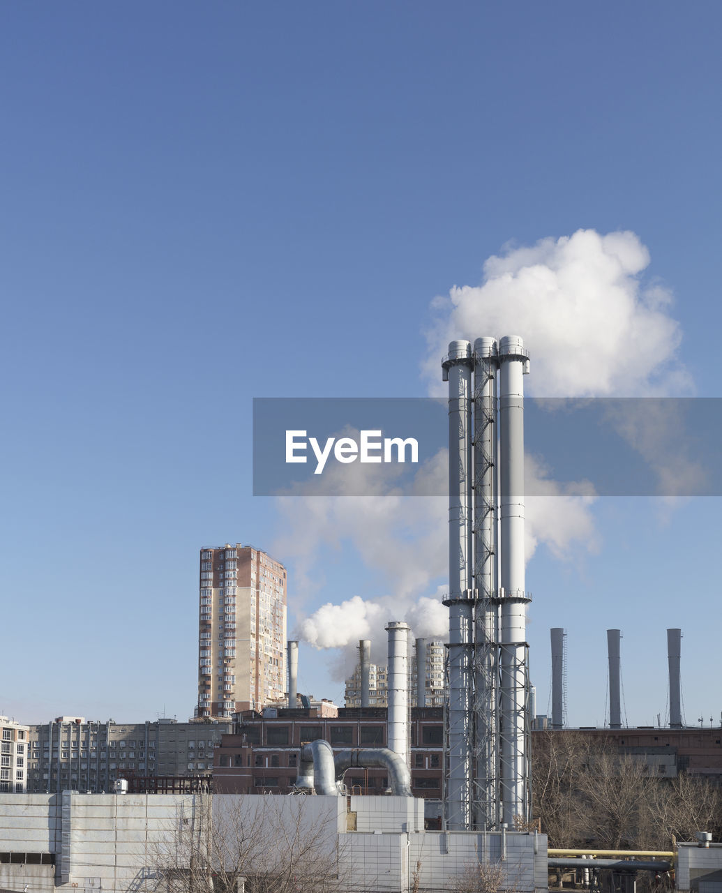 building exterior, built structure, architecture, factory, industry, sky, smoke stack, environmental issues, pollution, smoke - physical structure, no people, nature, fuel and power generation, industrial building, day, emitting, tall - high, outdoors, chimney, environment, air pollution, chemical plant