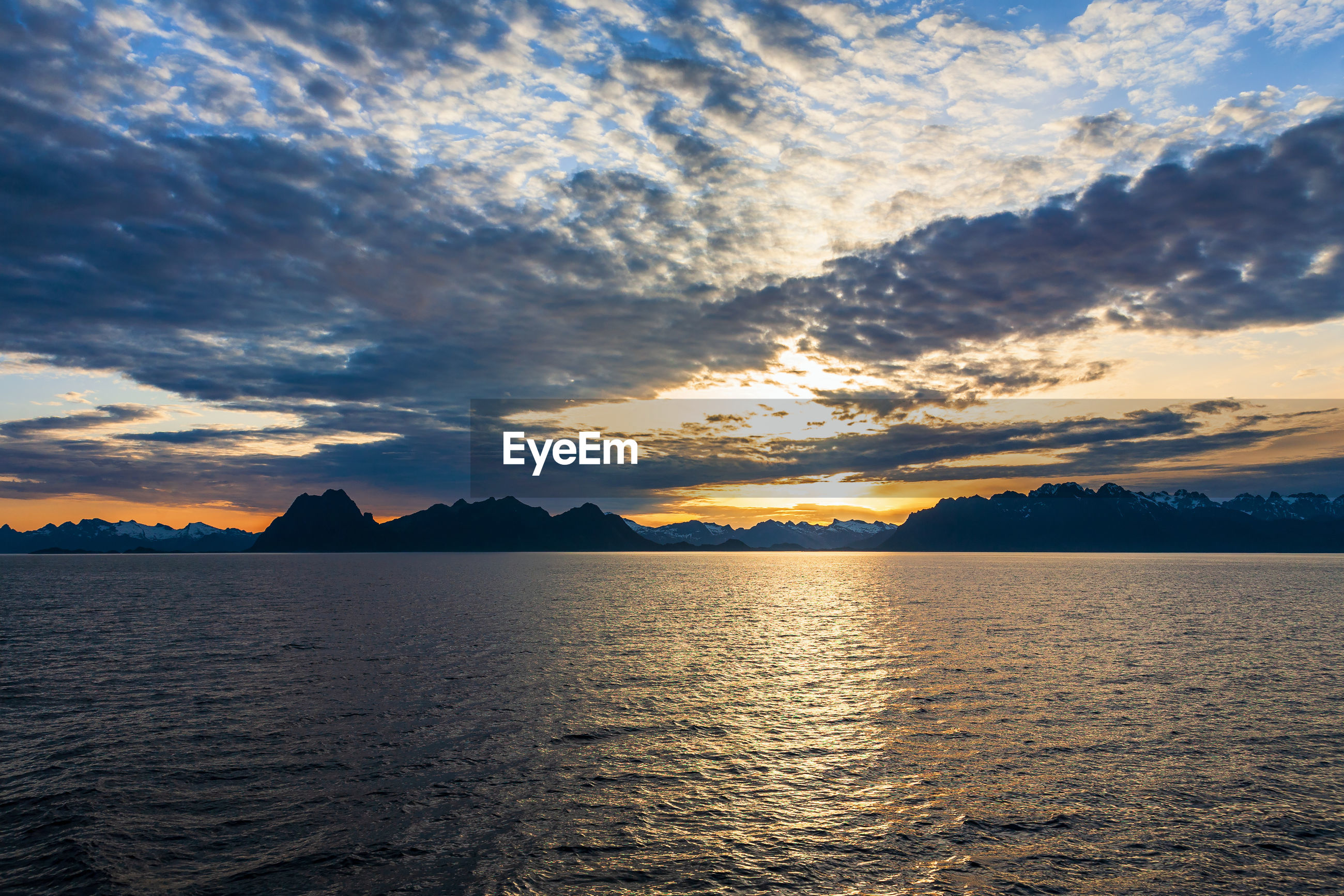 SCENIC VIEW OF SEA BY SILHOUETTE MOUNTAINS AGAINST SKY