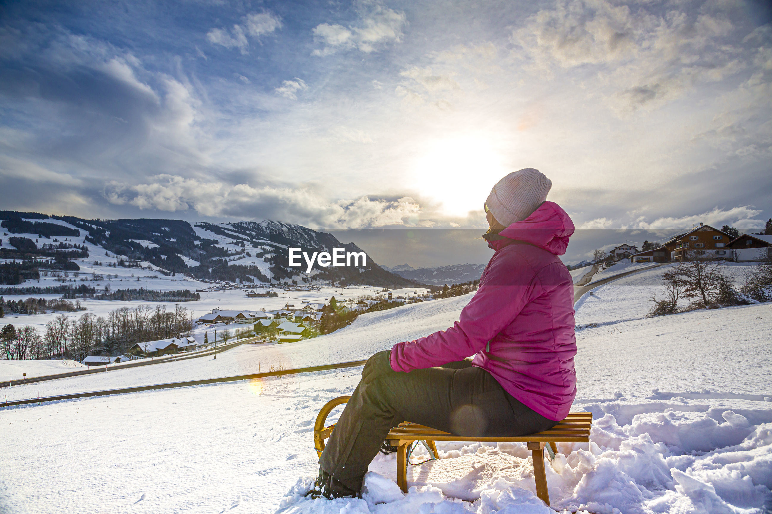 Full length of woman sitting on sled during winter