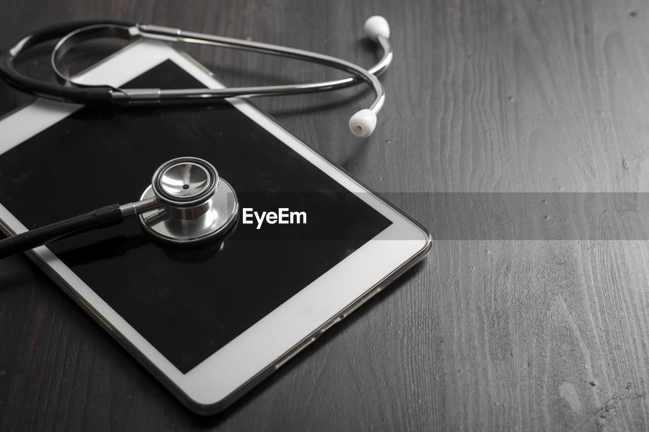 table, indoors, medical supplies, medical instrument, technology, still life, stethoscope, medical equipment, healthcare and medicine, no people, wood - material, single object, high angle view, close-up, medical exam, communication, music, equipment, wireless technology, connection, care, pulse trace