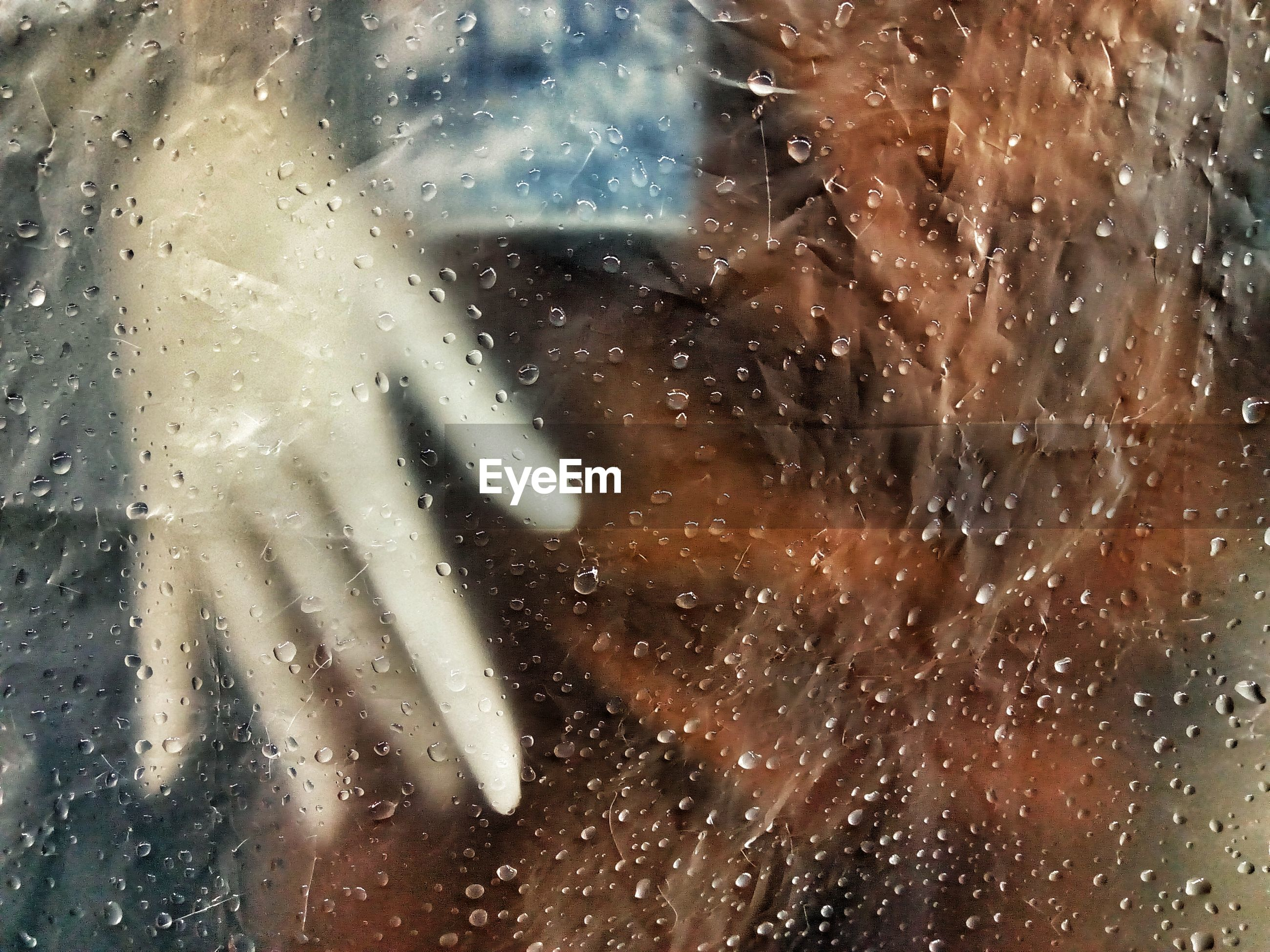 Hand seen through wet plastic