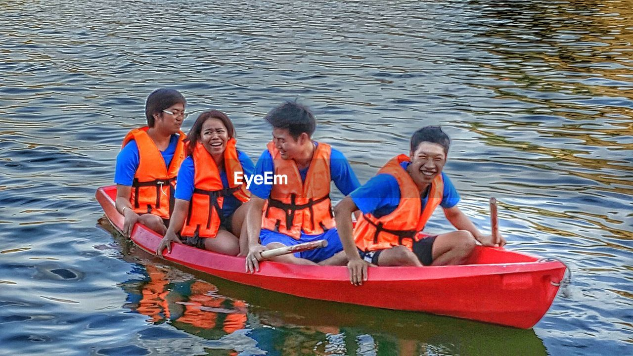 life jacket, leisure activity, oar, boys, child, childhood, smiling, togetherness, adventure, outdoors, day, vacations, water, portrait, kayak, elementary age, summer, father, nautical vessel, sitting, males, men, looking at camera, adult, women, nature, full length, happiness, sea, people