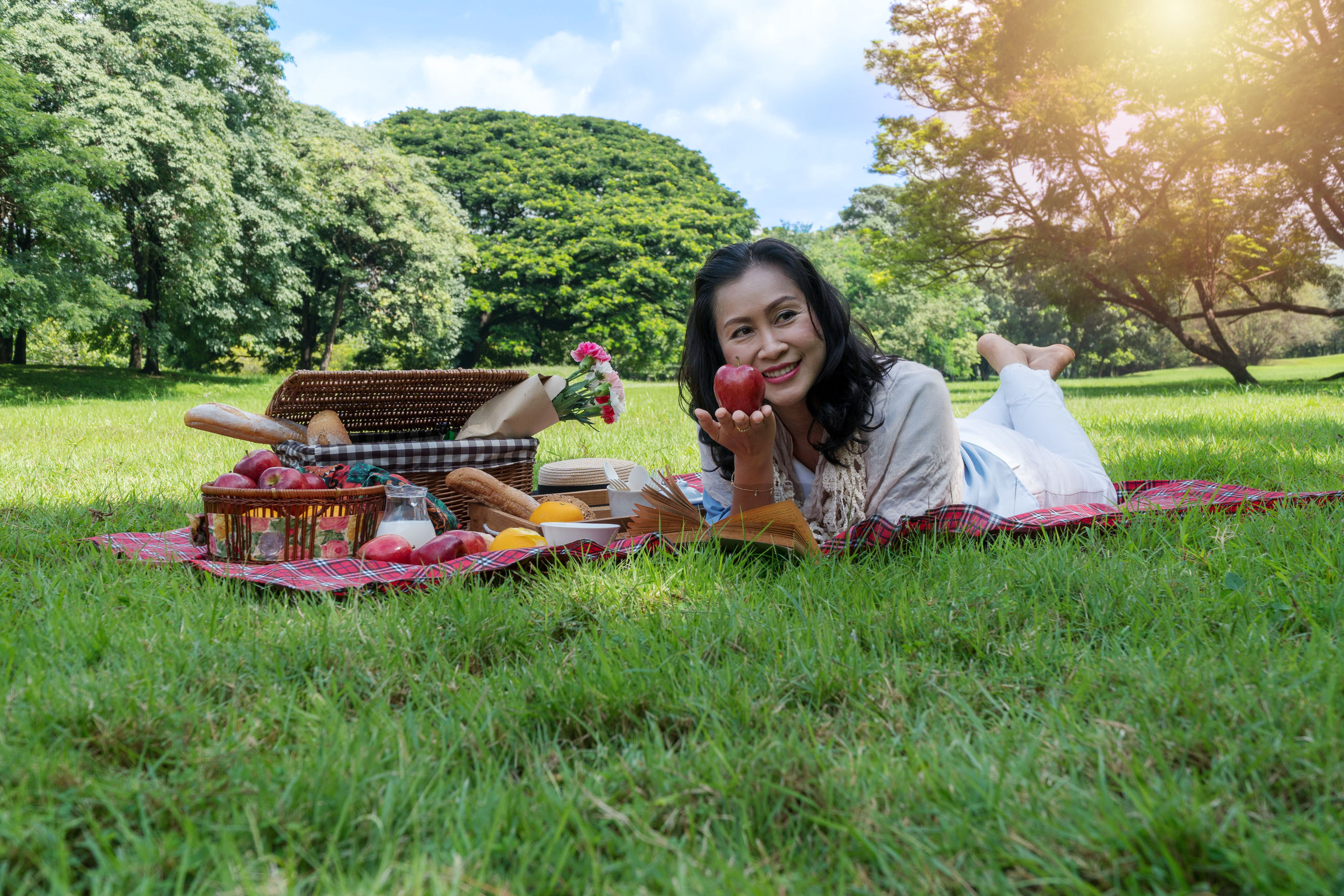 Smiling young woman holding apple while lying on grass