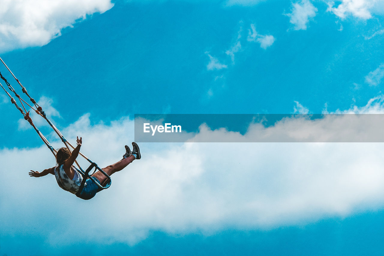 Low Angle View Of Woman Swinging Against Cloudy Sky