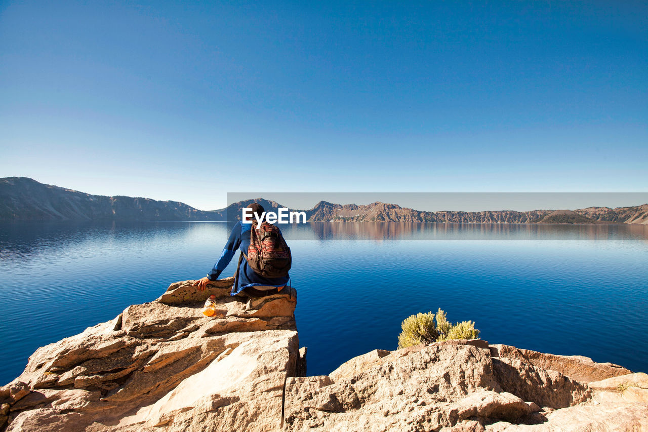 Man Sitting On Rock At Lake Against Clear Blue Sky