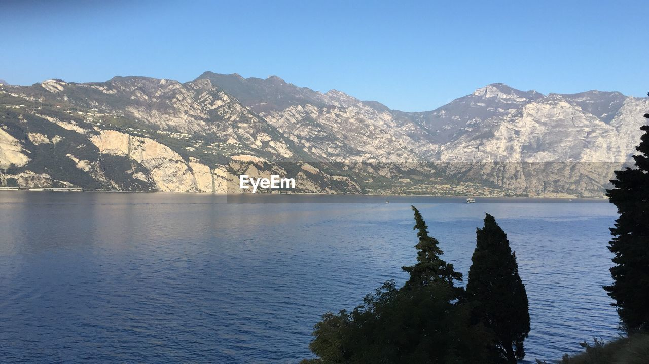 mountain, mountain range, scenics, nature, beauty in nature, tranquility, tranquil scene, water, rock - object, day, no people, outdoors, waterfront, clear sky, landscape, lake, physical geography, sky, view into land