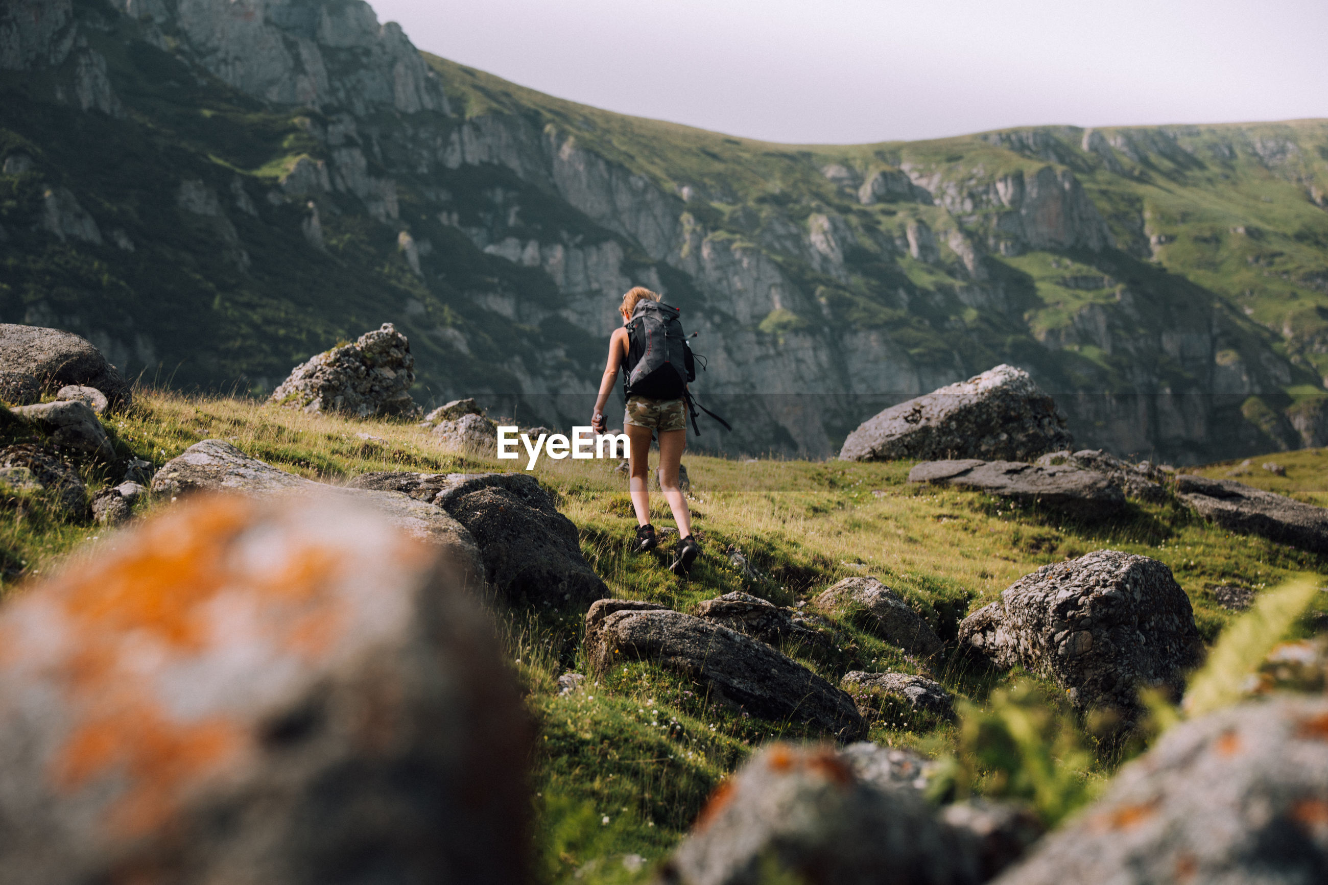 Low angle view of female hiker with backpack walking on mountain
