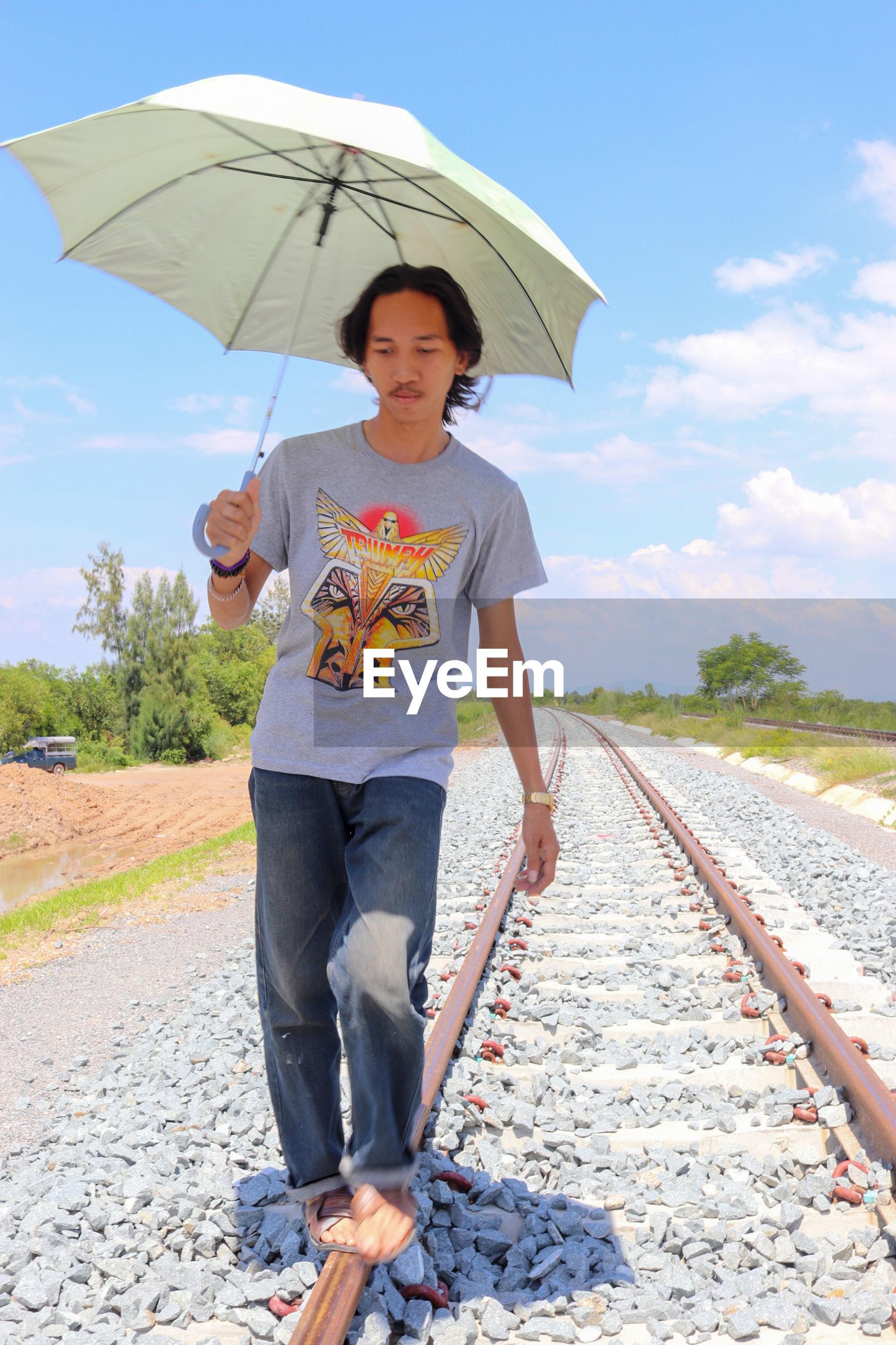 Full length of man holding umbrella while walking on railroad track