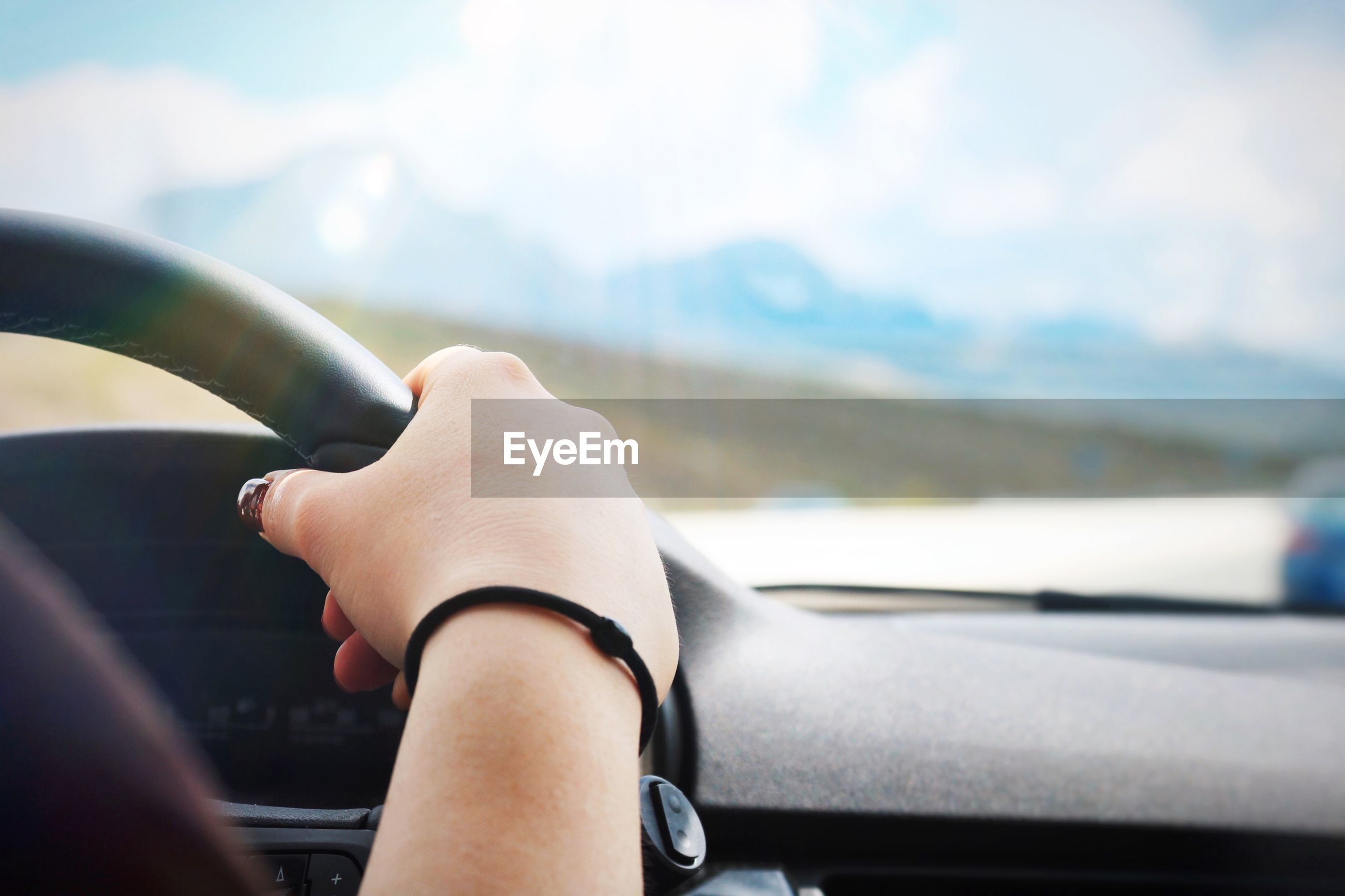 Cropped hand of woman holding steering wheel in car
