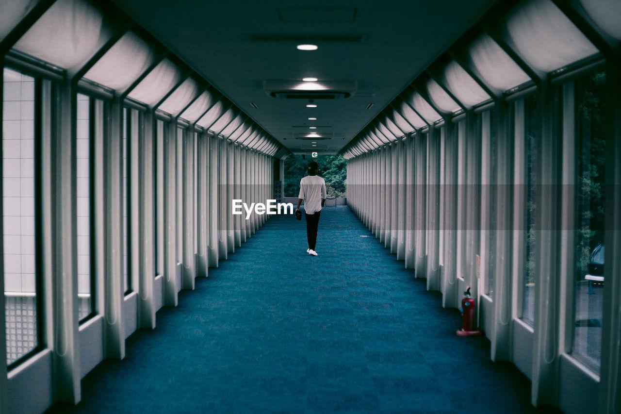Rear View Of Man Walking In Empty Corridor Of Building