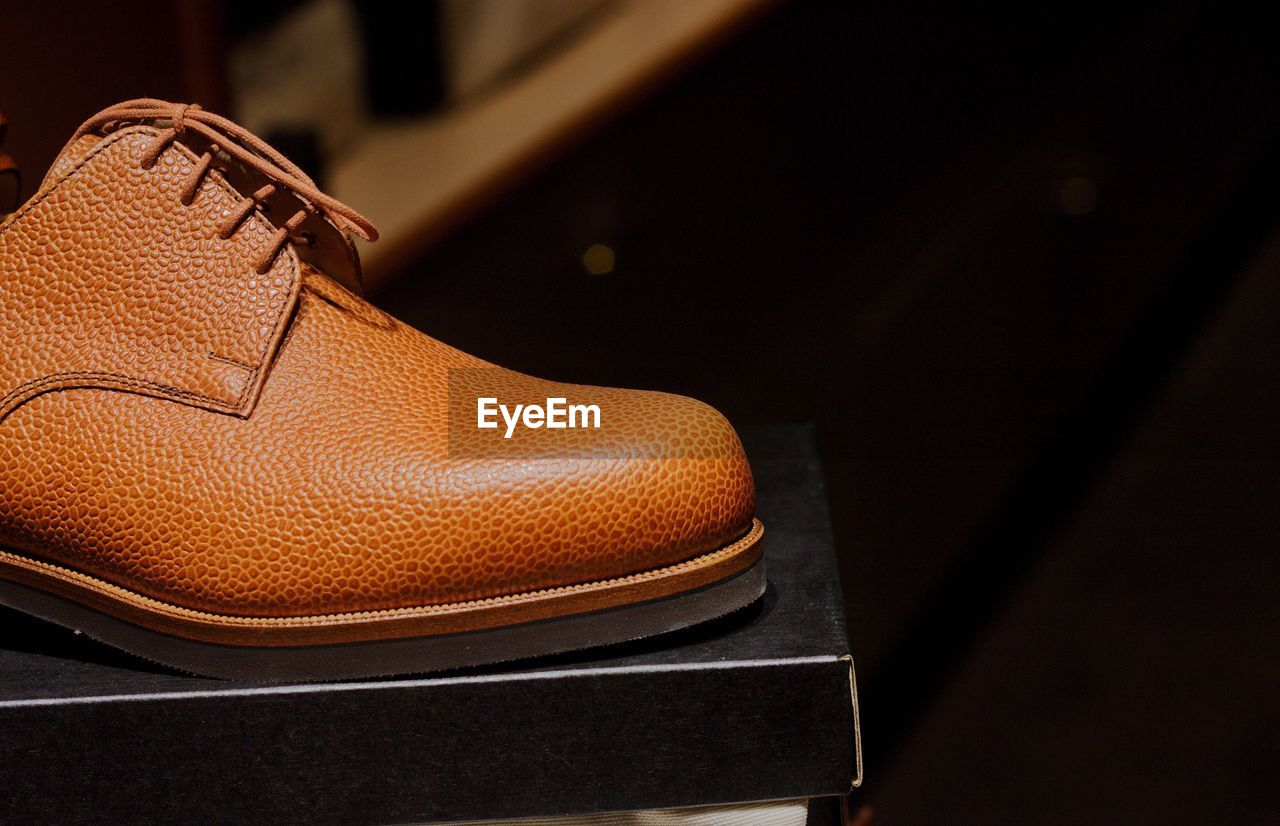 shoe, close-up, indoors, brown, leather, no people, still life, personal accessory, fashion, focus on foreground, clothing, pair, seat, high angle view, shoelace, table, bag, single object, selective focus, casual clothing, menswear
