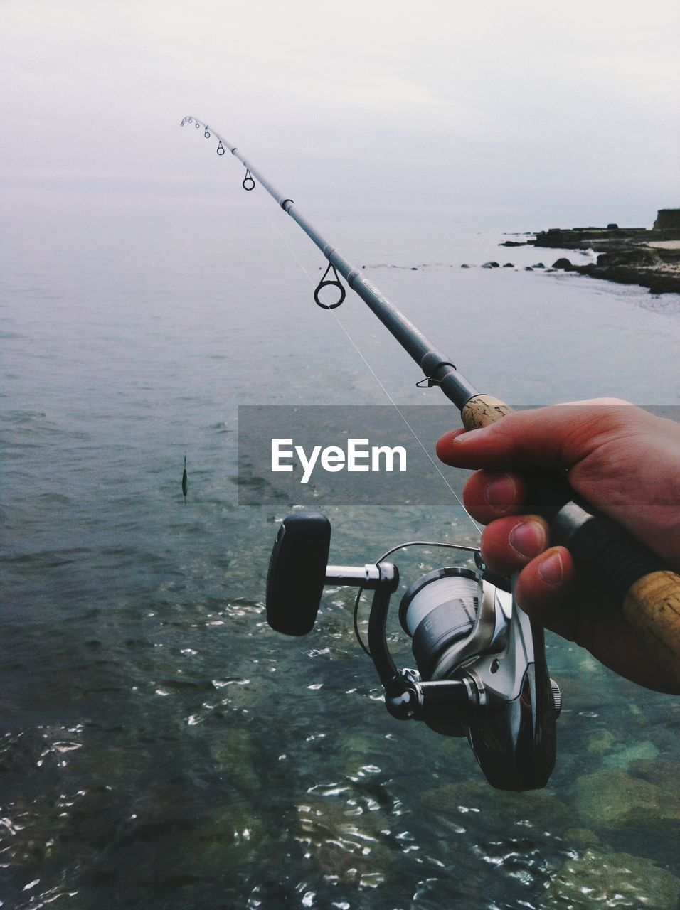 Fishing rod holding by man