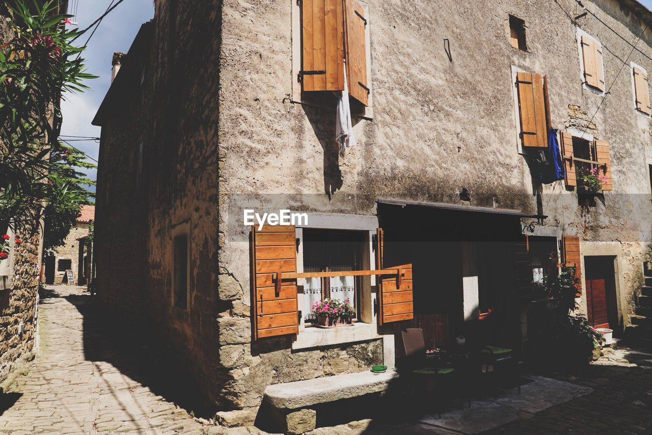 built structure, building exterior, architecture, building, residential district, day, city, no people, nature, sunlight, house, outdoors, window, street, wall - building feature, hanging, shadow, wall, travel destinations, direction, alley, street market