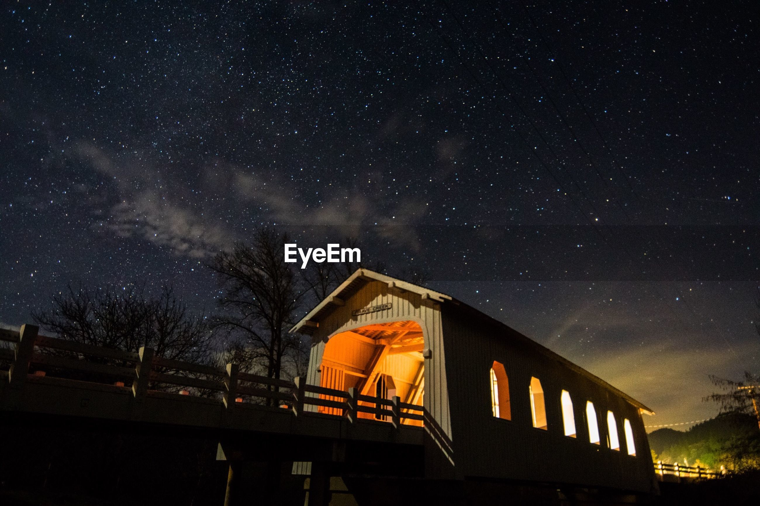 Low angle view of covered bridge against sky at night