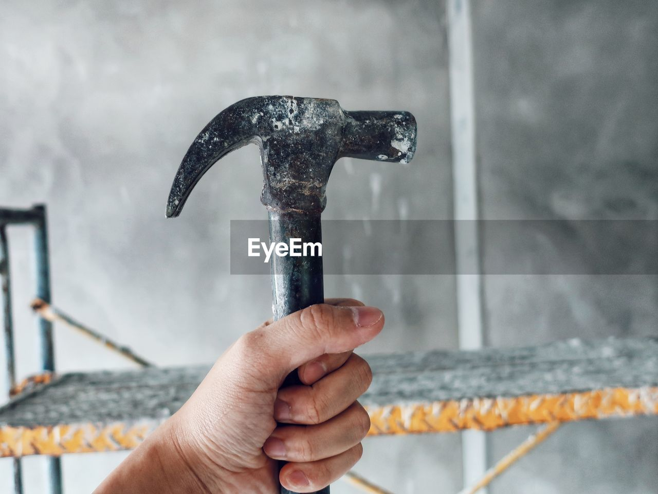 Close-Up Of Hand Holding Hammer At Construction Site