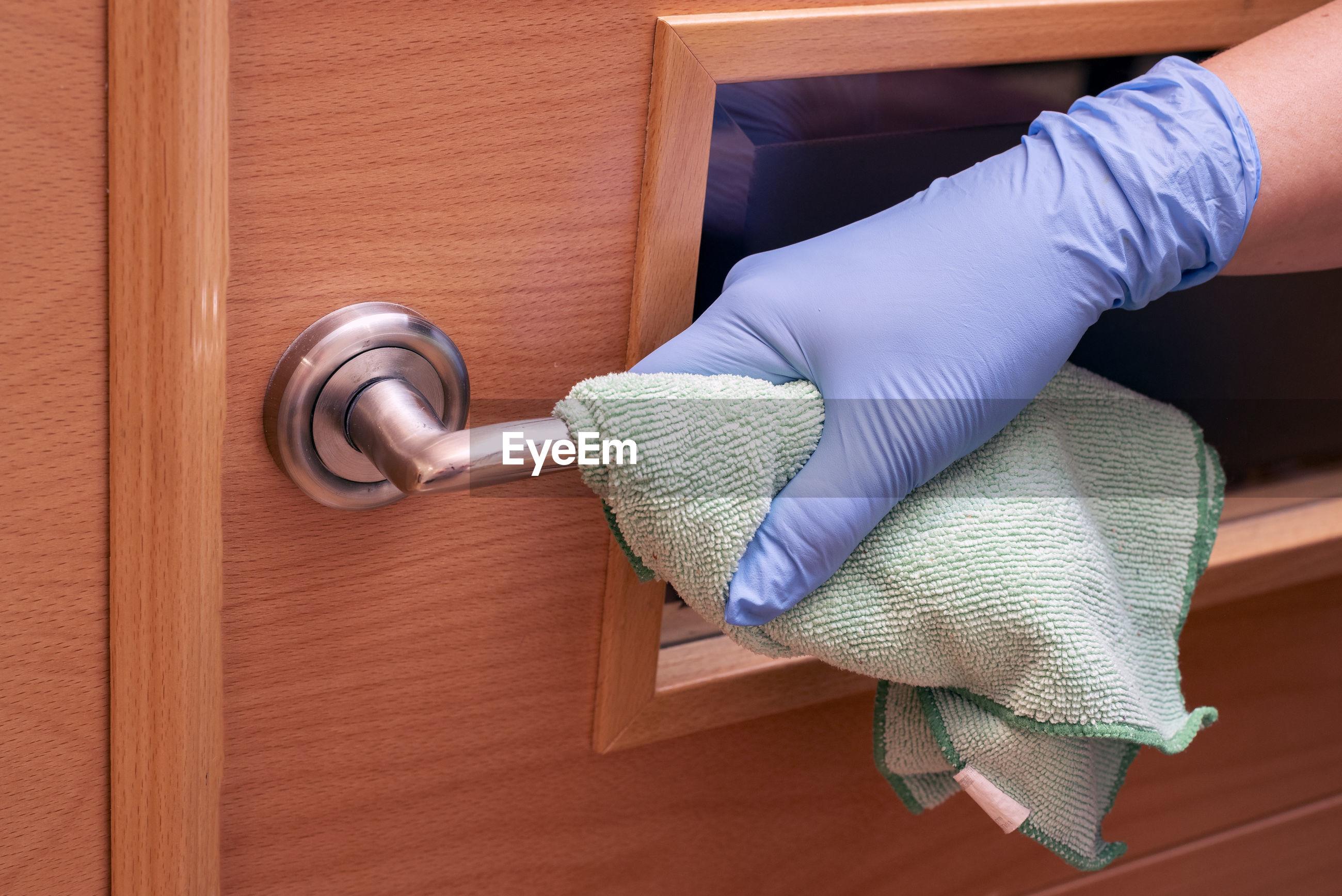 Close-up of human hand on wooden door