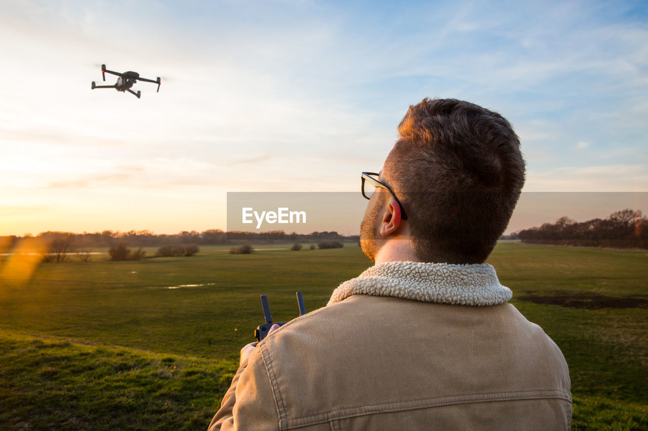 air vehicle, sky, real people, one person, sunset, transportation, airplane, men, rear view, leisure activity, nature, mode of transportation, flying, field, lifestyles, headshot, land, cloud - sky, mid-air